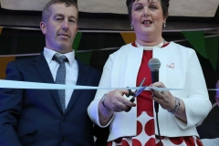 Noreen Mc Garvey cuts the ribbon to officially open the Burtonport festival on Saturday night in the company of committee member Paddy Bonner.