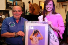 Kevin Bonner of Bonner's, Dungloe presenting a painting to outgoing Mary from Dungloe winner Caroline O'Donnell of her winning moment as captured last year by photographer Eoin Mc Garvey. Kevin has been involved with the Mary festival for many years.